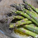 seasoning asparagus in olive oil and salt